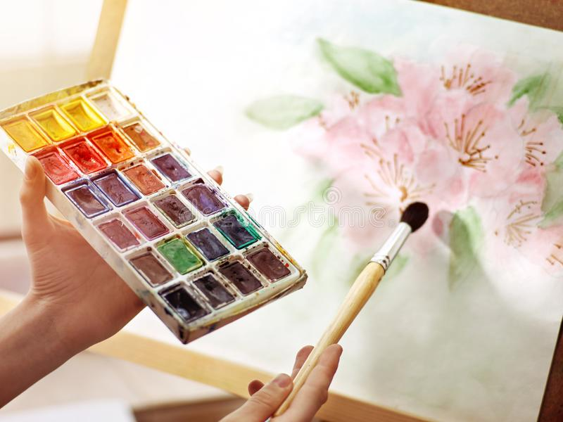 Artist painting on easel studio. Girl hands paints with brush. stock photo