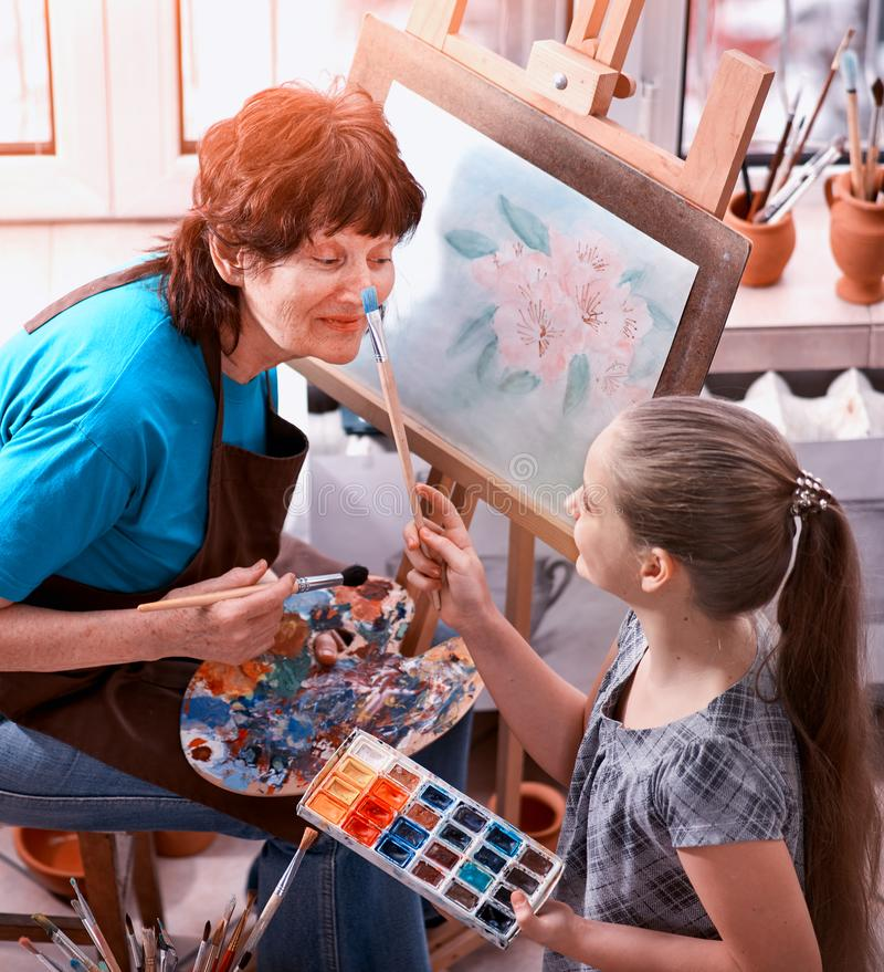 Artist painting easel in studio. Authentic grandmother and kids. Artist painting easel in studio. Authentic old women and kids girl paints with palette stock photography
