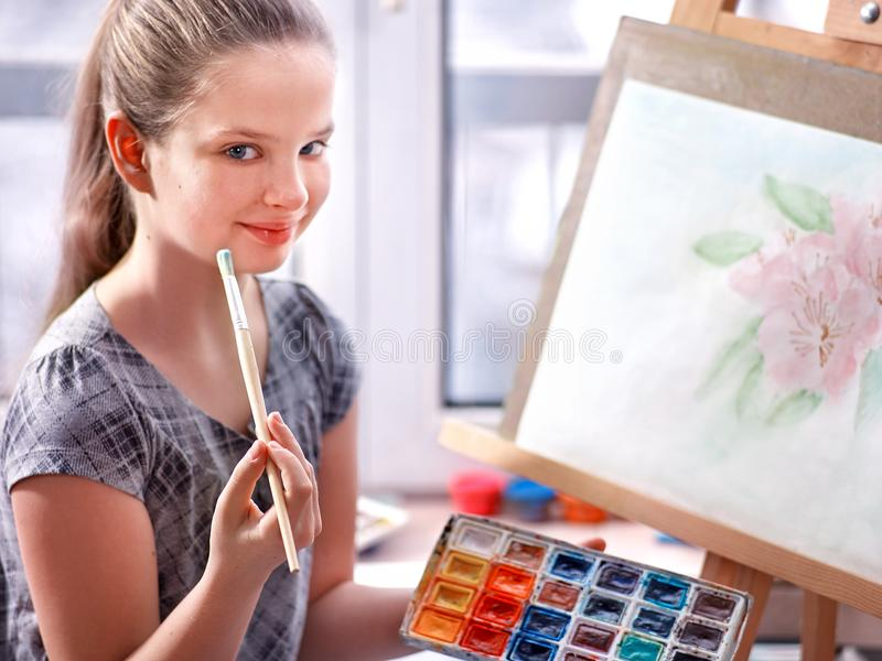 Artist painting on easel in studio. Girl paints with brush. Artist painting on easel and palette in studio. Authentic girl paints with oil brush in morning stock images
