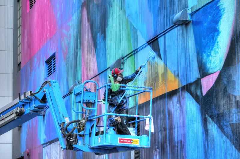 Artist painting mural on building in Sacramento stock photos