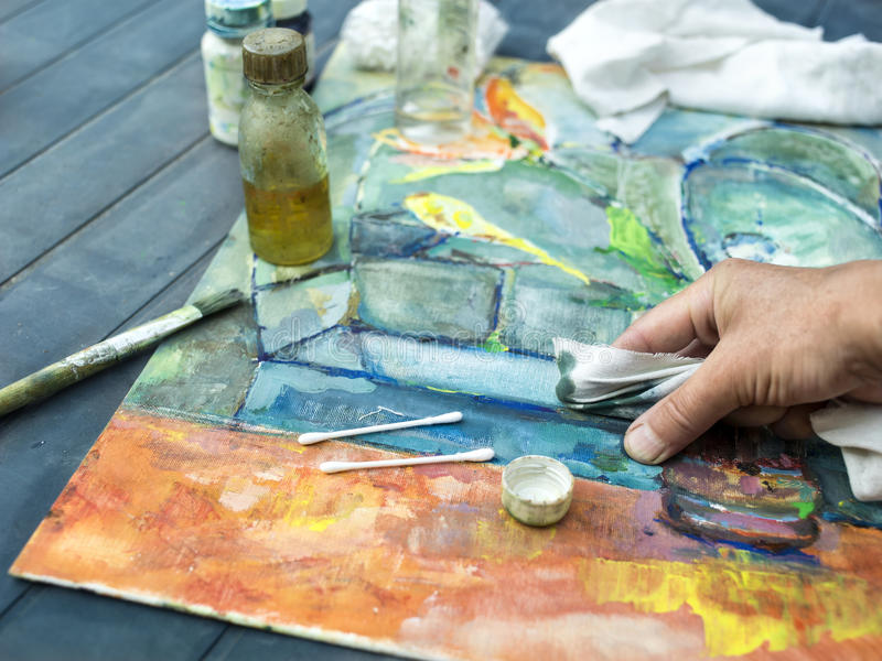 Artist And Painting Technique. Artist hand with cloth demonstrating a painting technique. Outdoor selective focus shot royalty free stock photo