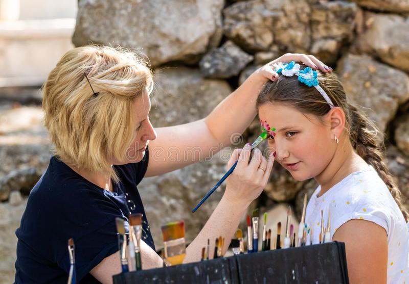 The artist paints a drawing on the face of the girl at the annual festival Jerusalem Knights. Jerusalem, Israel, September 30, 2019 : The artist paints a drawing stock images