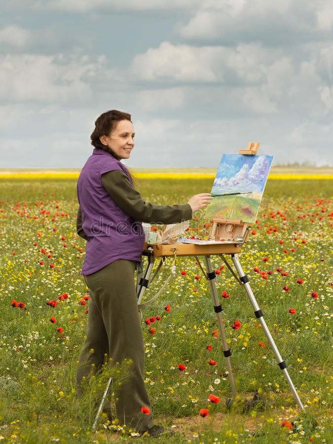 Artist paints picture with brush on the poppy field stock image