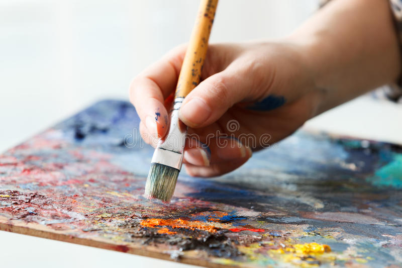 Artist paints a picture of oil paint brush in hand with palette. Close up stock photo