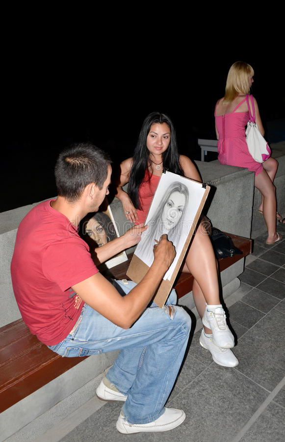 The artist paints a portrait of a beautiful woman on the embankment of Yalta in the Crimea. Profession, occupation.Yalta, Crimea stock image