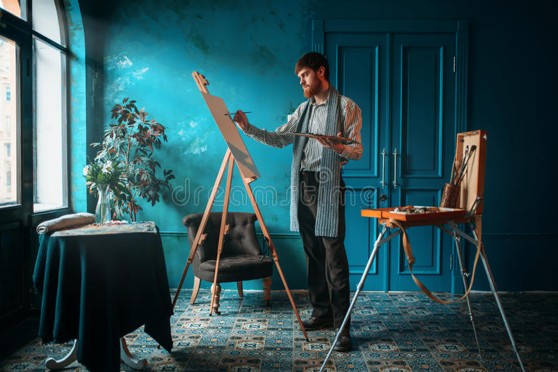 Artist with palette and brush paint on easel stock image