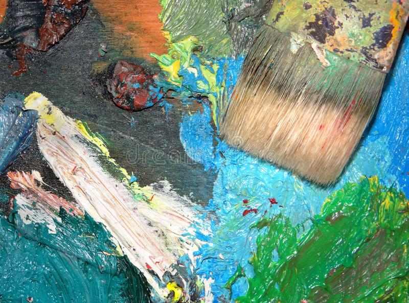 Artist`s brush and brush strokes on the palette. Close-up stock photo