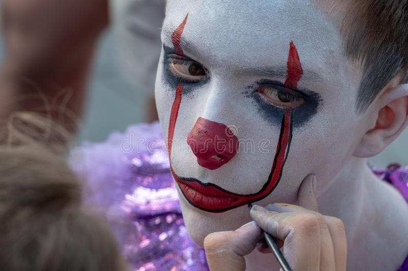 Street makeup. The image of a clown or mime. Costume for carnival or holiday halloween. Cosplay at a horror party. Artist`s hand stock photography