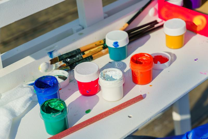 Artist`s work place. Open multicolored gouache, paint brushes and pencil on white table royalty free stock photo