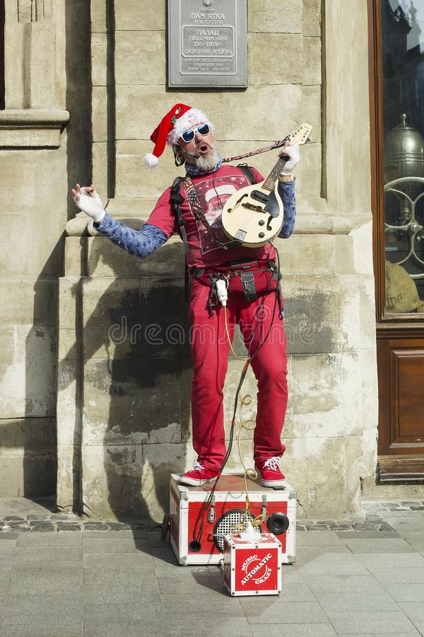 Artist in Santa Claus red costume sings and plays electric guitar stock images