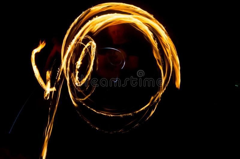 The artist shows a fire show at night spinning torches, circles of fire and loops stock photo