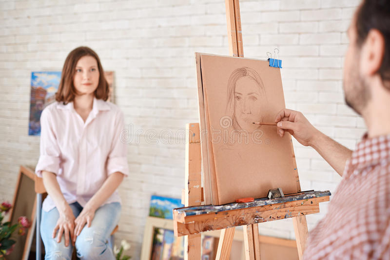 Artist Sketching Portrait of Beautiful Model in Art-Studio royalty free stock photos