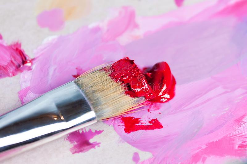 The artist squeezed the paint onto the palette and mixes the pink paint with a synthetic brush. You can see the artist`s fingers in the paint royalty free stock images