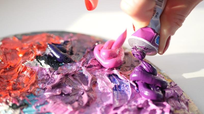 Artist squeezes from the tube to the palette purple oily pink paint , HD. royalty free stock image