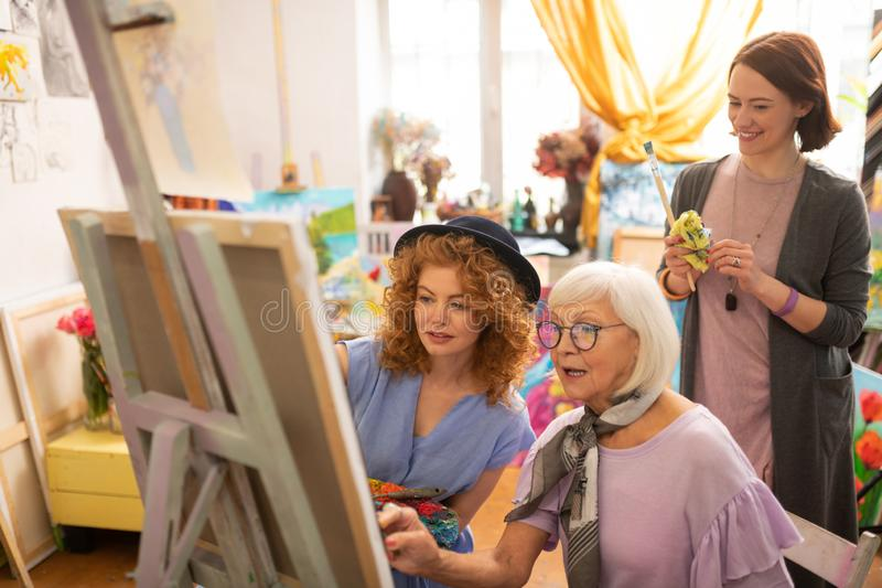 Artist standing behind her aged teacher and friend royalty free stock photos