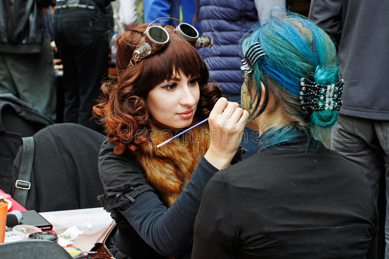 Artist in steampunk style creating makeup for young woman at the festival `Bright people` on City Day on Neglinaya street in Mosco stock photo