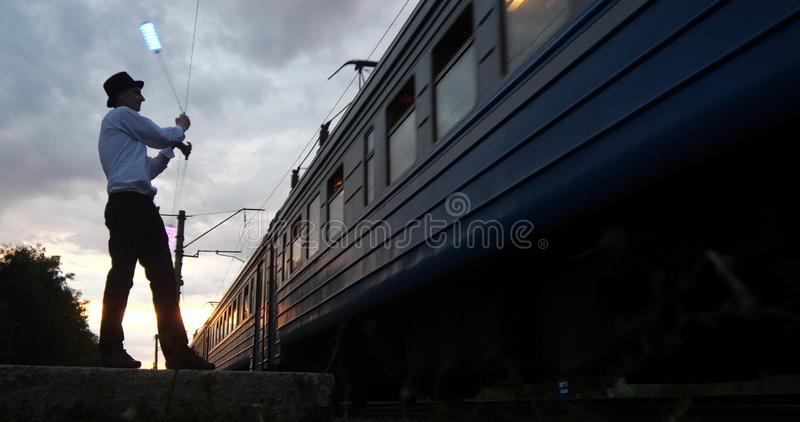 Artist at sunset makes danger trick on the railway near movement train. royalty free stock photos