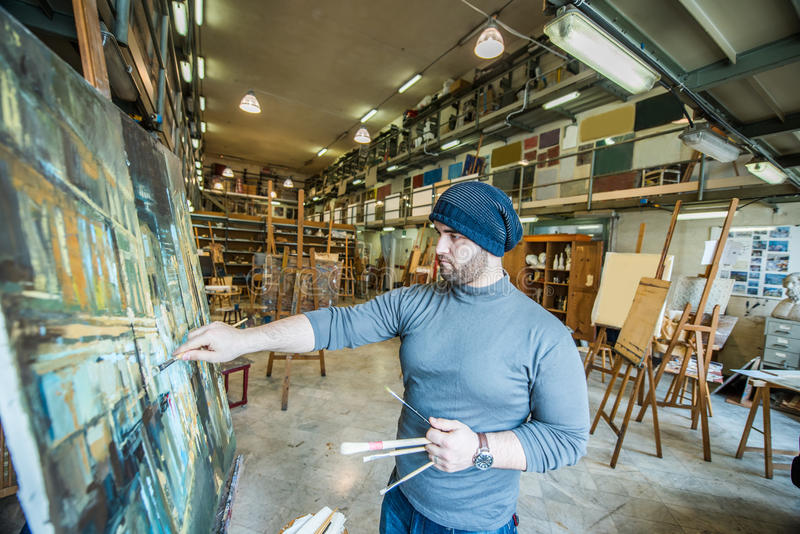 Artist/teacher painting and artwork in his art studio royalty free stock image