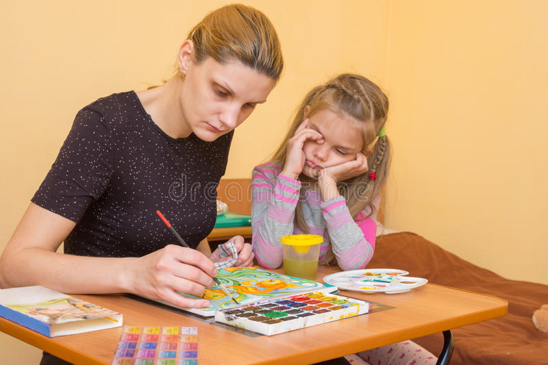 Artist teacher shows how to paint watercolors, and the child rubs his eyes. Wearily stock image
