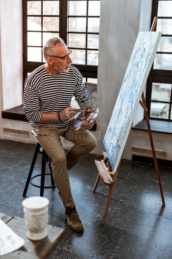 Artist wearing beige trousers and striped shirt working on new canvas. Aged artist. Aged grey-haired artist wearing glasses wearing beige trousers and striped stock photo