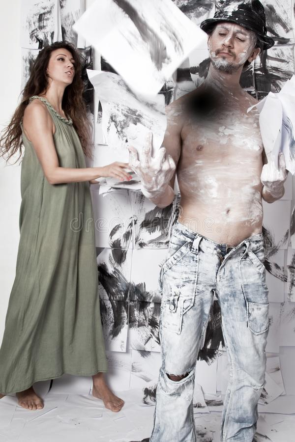 Artist and woman-assistant. Painting wall Background stock photography