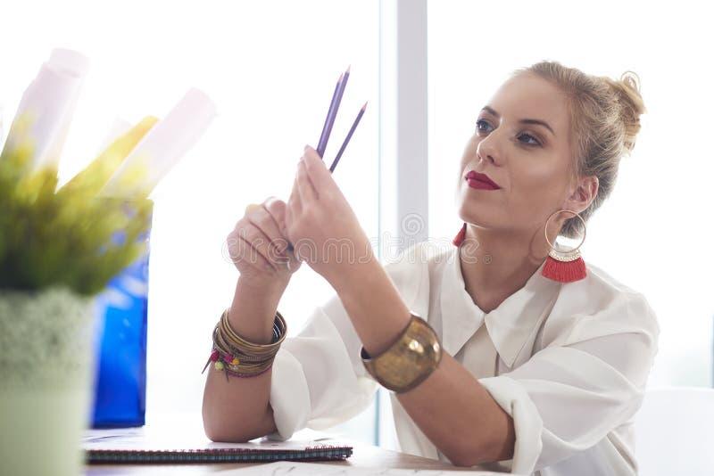 Artist woman working at the workshop. Fashion designer sharpened her pencils stock images