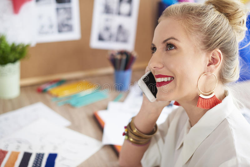 Artist woman working at the workshop. Woman having conversation by the phone royalty free stock images