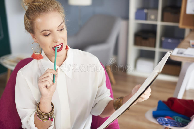 Artist woman working at the workshop. Woman holding pencil in her mouth royalty free stock images
