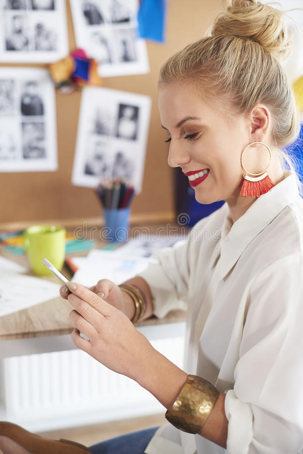 Artist woman working at the workshop. Woman sending messages by the smartphone stock photos