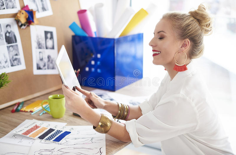 Artist woman working at the workshop. Setting up her own design website royalty free stock image