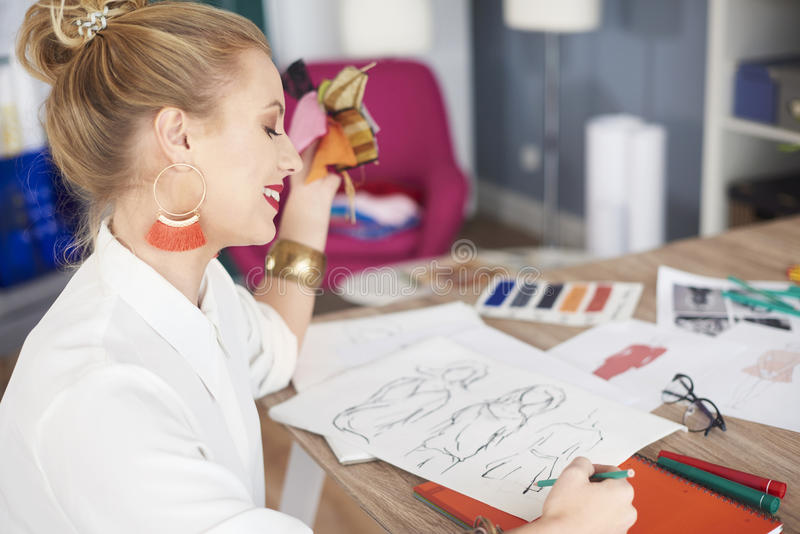 Artist woman working at the workshop. Woman sketching few designs of new collection stock images