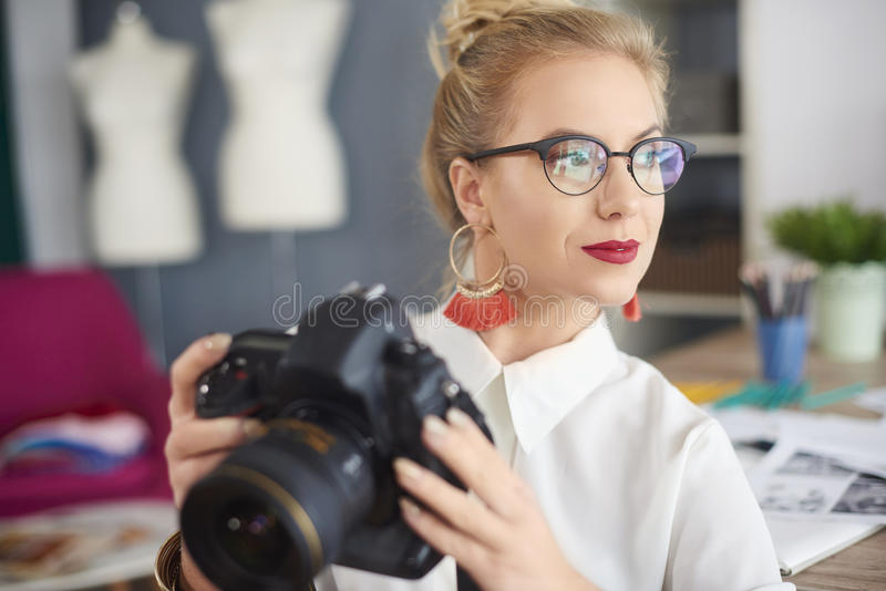 Artist woman working at the workshop. Thoughtful young woman holding camera royalty free stock images