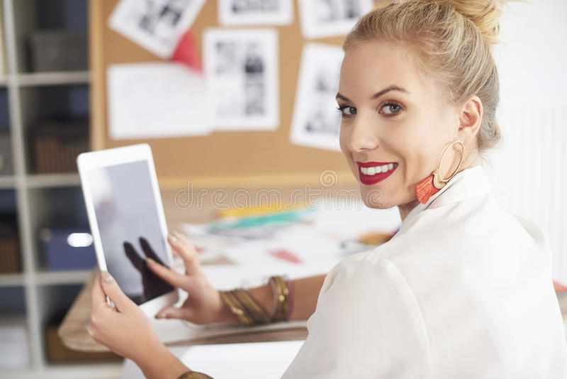 Artist woman working at the workshop. Turning woman with digital tablet on hands stock photo