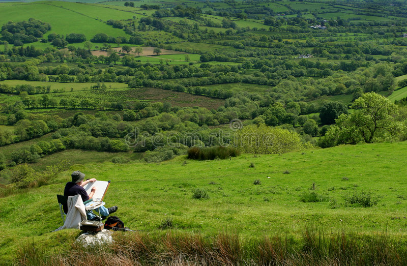 Artist At Work. Artist sitting in a chair, next to his artists equipment, starting to draw the landscape of fields and trees. Set in the Cambrian mountains