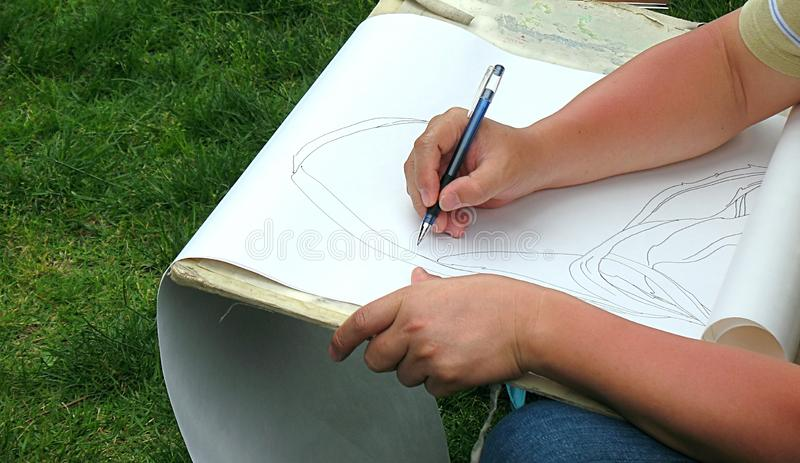 Artist at Work. A draftsman is drawing a nature scene with a pencil royalty free stock images