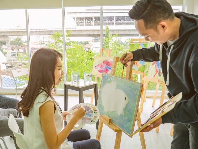 Artista asiático novo considerável Teaching da cor do homem ou de água como pintar e estudante Learning do artista a classe fotos de stock royalty free