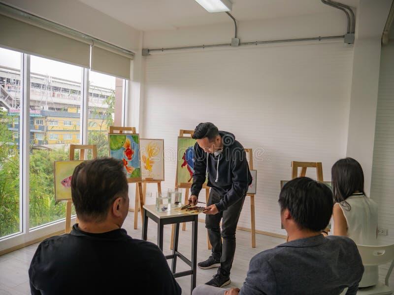 Artista asiático novo considerável Teaching da cor do homem ou de água como pintar no estúdio imagem de stock royalty free