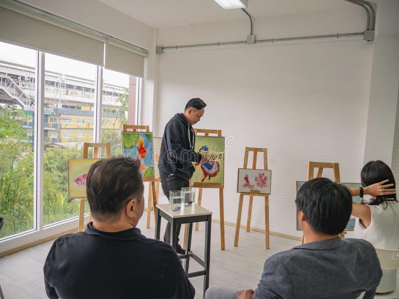 Artista asiático novo considerável Teaching da cor do homem ou de água como pintar no estúdio imagens de stock royalty free