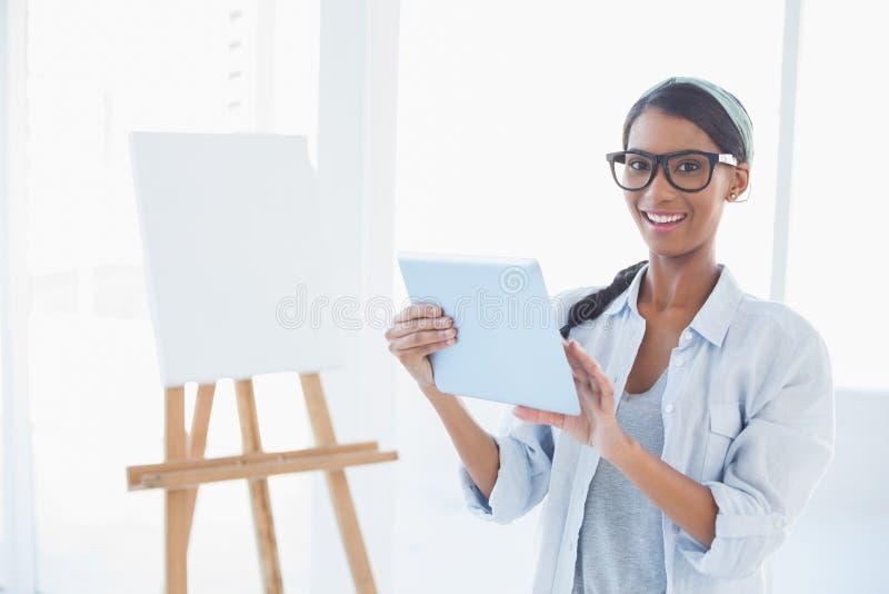 Artista attraente felice che per mezzo del suo pc della compressa fotografia stock libera da diritti