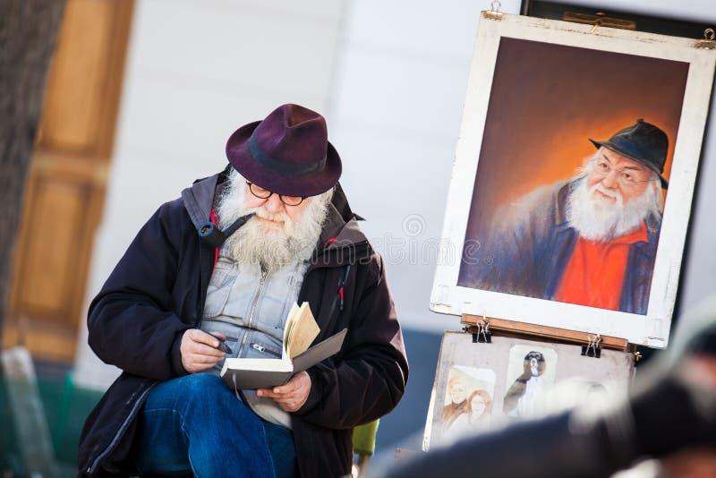 Artista barbuto senior che lavora al Place du Tertre famoso nel Montmartre fotografia stock