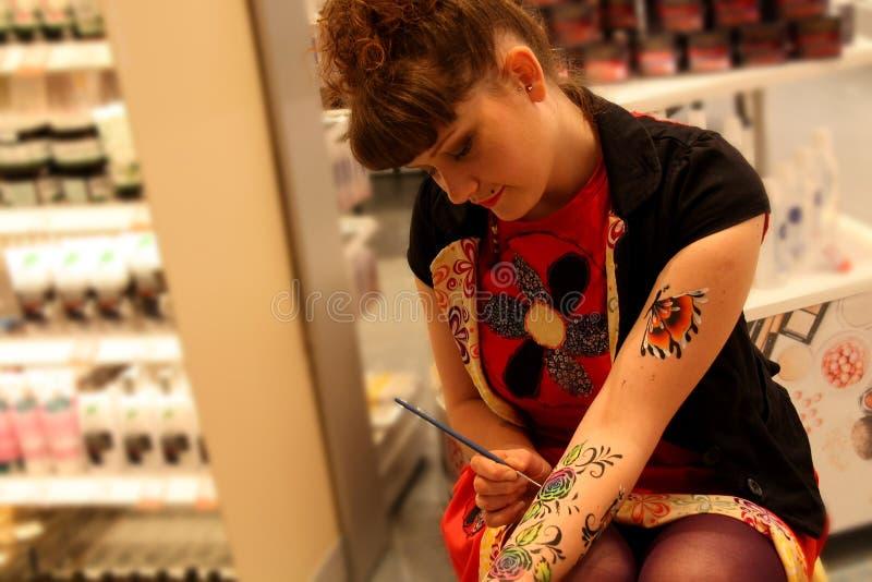 Artista bonito Painting em sua mão ao esperar em um cliente imagem de stock royalty free