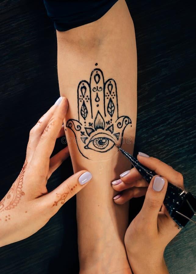 Artista che applica il tatuaggio di mehndi del hennè sulla mano femminile fotografie stock