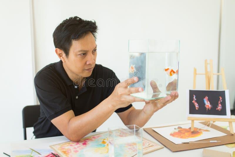 Artista che guarda alla ciotola del pesce per la sua ispirazione alla verniciatura immagine stock libera da diritti