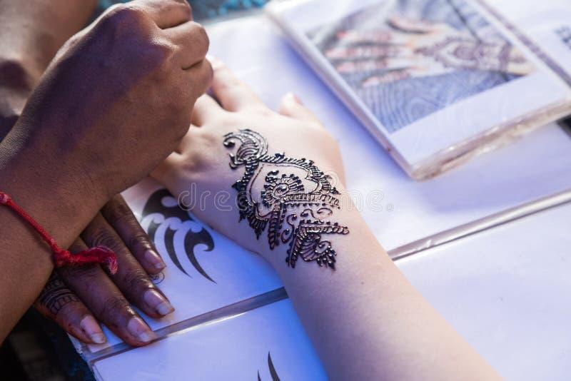 Artista che innesta arte temporanea del tatuaggio di mehendi del hennè sull'aletta della mano immagine stock libera da diritti