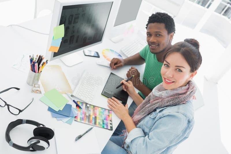 Artista con il disegno del collega qualcosa sulla tavola del grafico fotografia stock