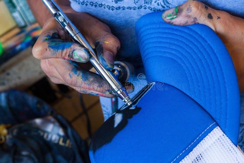 Artista con l'aerografo che colora un cappello blu immagini stock