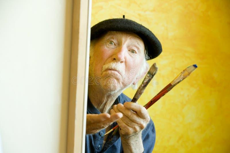 Artista con un berreto ad una tela di canapa che esamina modello fotografia stock