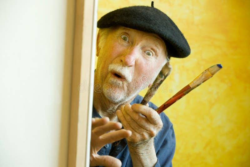 Artista con un berreto ad una tela di canapa che esamina modello fotografie stock