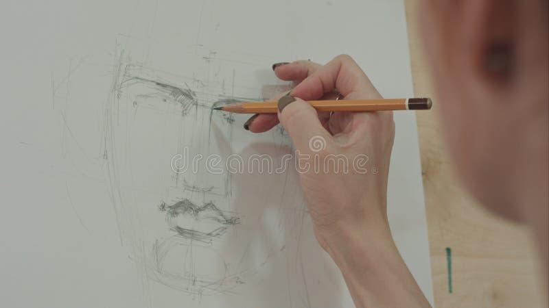 Artista concentrado de la mujer que pinta el retrato clásico del hombre con el lápiz fotos de archivo