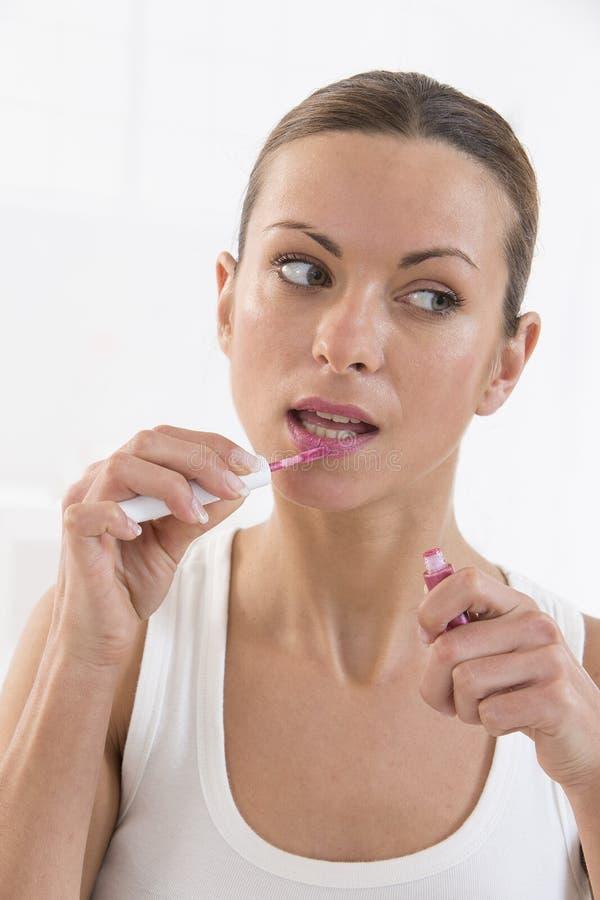 Artista da jovem mulher que aplica o batom ou o bordo-brilho com uma escova o imagem de stock